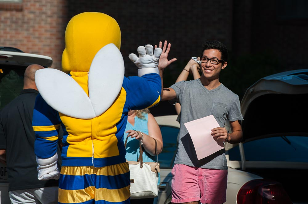 student high-fiving Rocky yellowjacket mascot