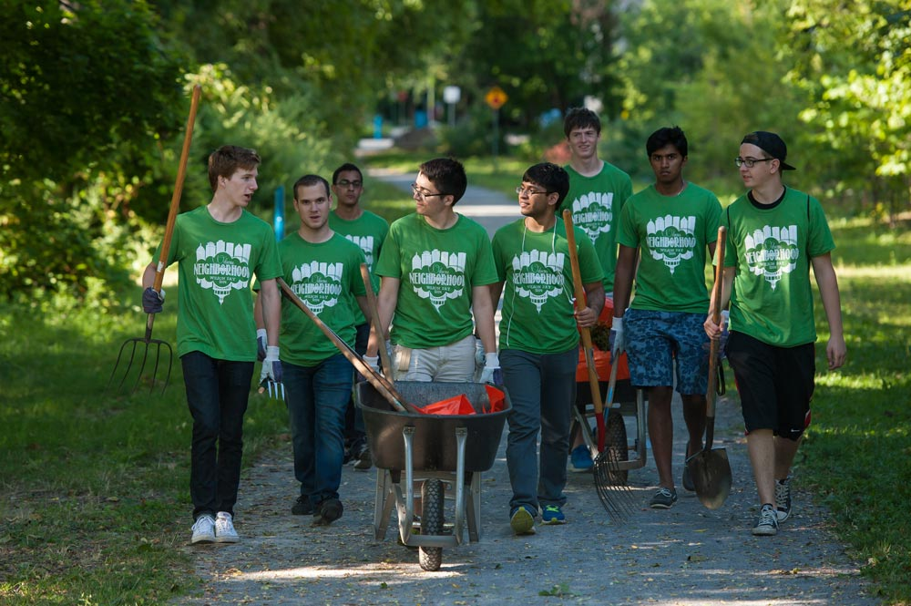 large group of students in matching t-shirts pushing wheelbarrows and carrying gardening equipment