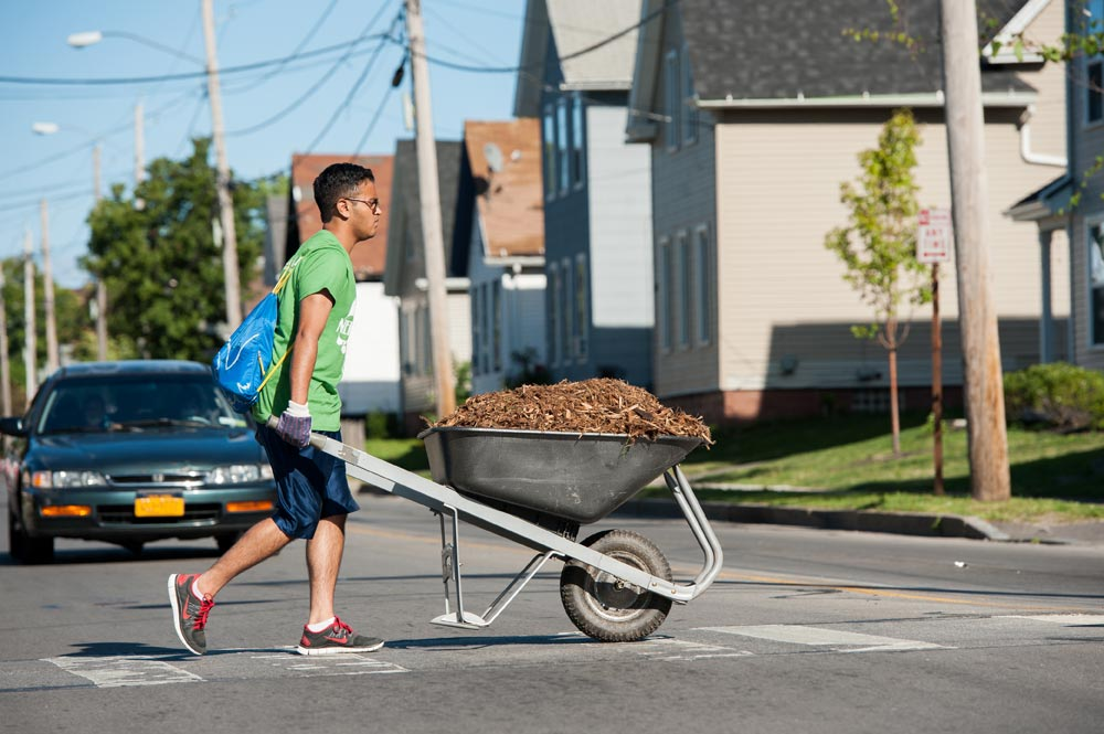 student pushing a wheelbarrow across a street