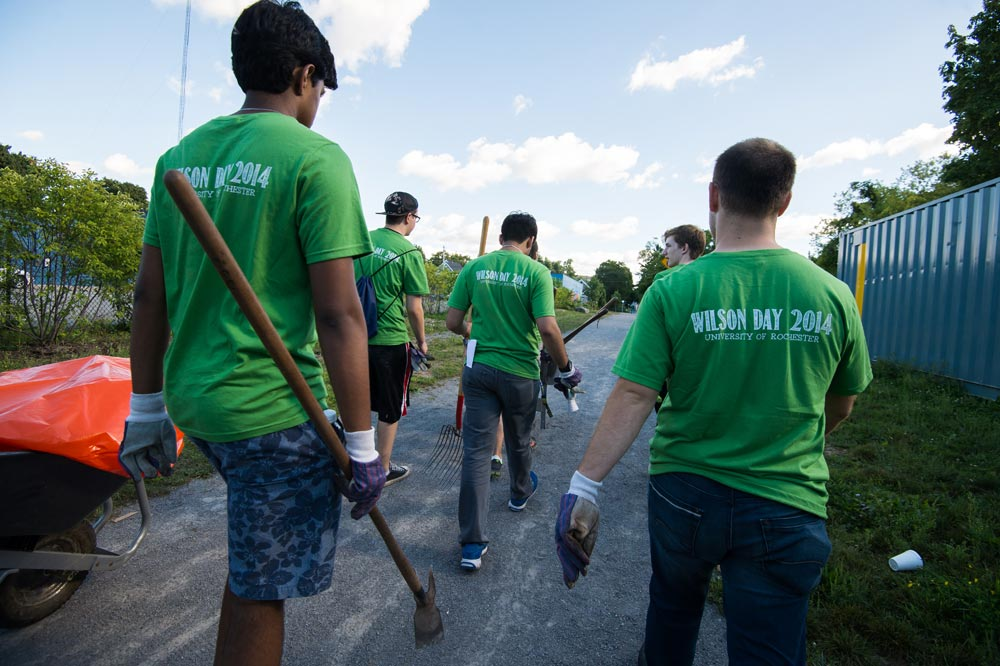 students walking down a road, the backs of their t-shirts read Wilson Day 2014