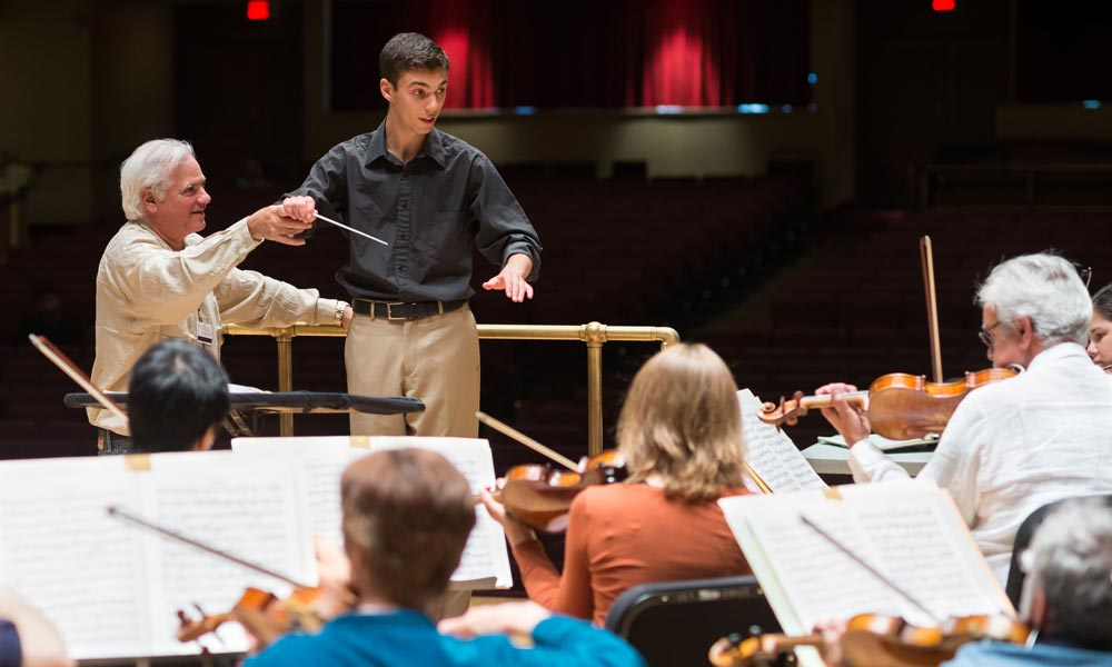 instructor holds the baton arm of a young conducting student who stands at the podium in from of orchestral musicians