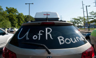 a car packed with stuff with the words UofR Bound painted on the rear window