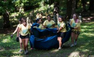 group of students pulls leaves on a tarp through Mt Hope Cemetery