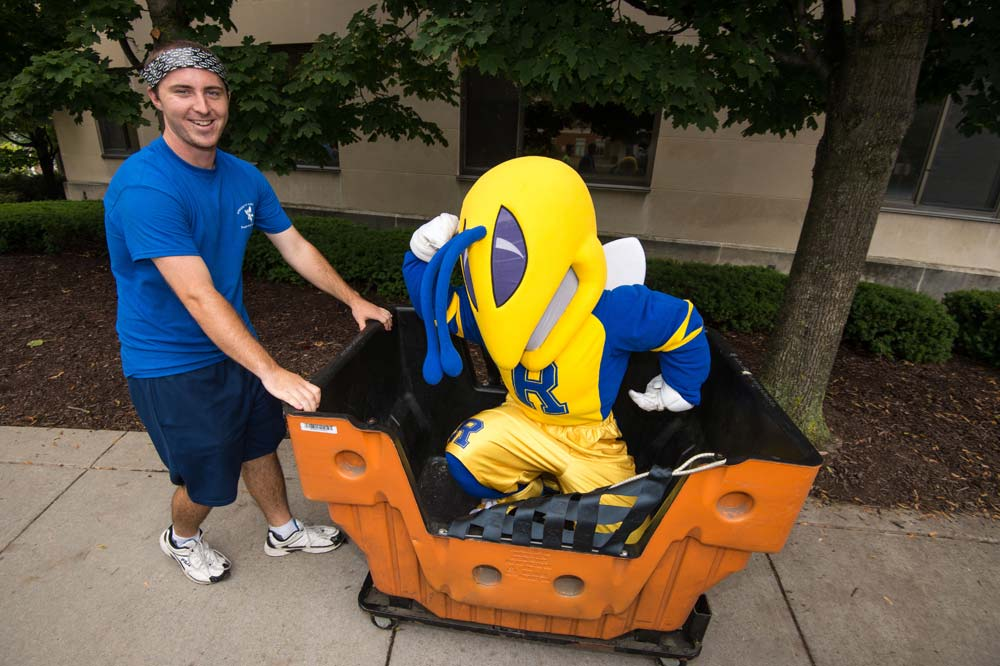 student pushes Rocky yellowjacket mascot in a luggage cart
