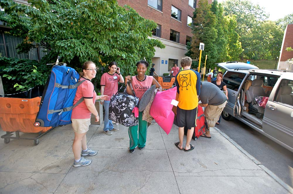 group of student helpers in matching t-shirts carrying pillows, suitcases