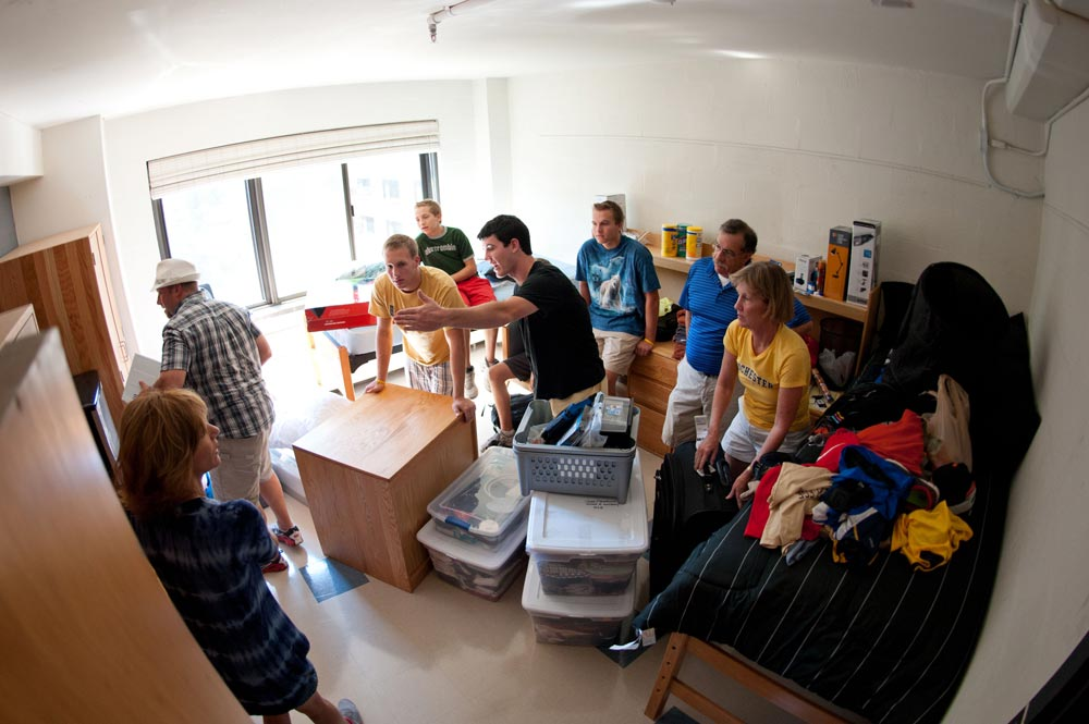 students and families re-arrange furniture in a dorm rool