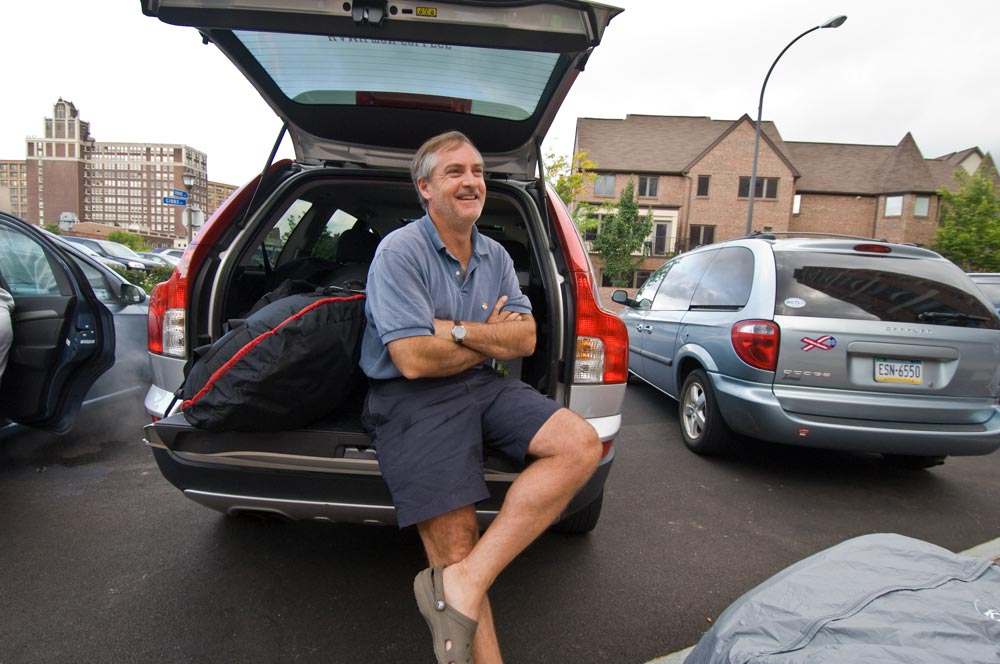 father sits in the bumper of his packed car and smiles