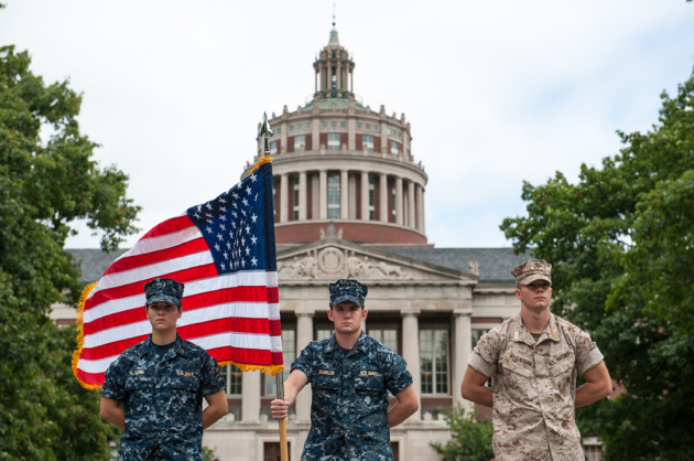 three NROTC midshipmen in uniform in front of Rush Rhees Library, one of them holding an American flag