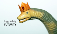 plastic dinosaur wearing a birthday hat with the text Happy Birthday Futurity