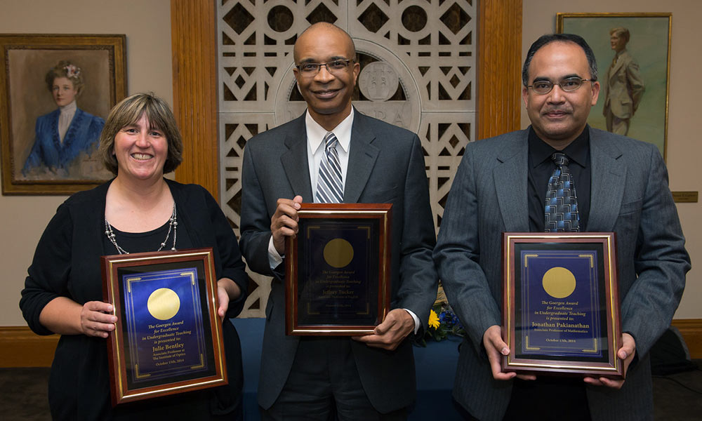 a woman and two men, holding plaques