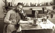 Santiago Ramón y Cajal at a table covered with microscopes