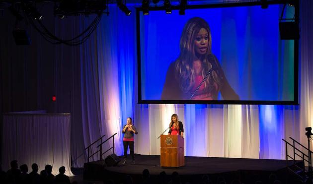 Laverne Cox on stage, with a giant screen projecting her image