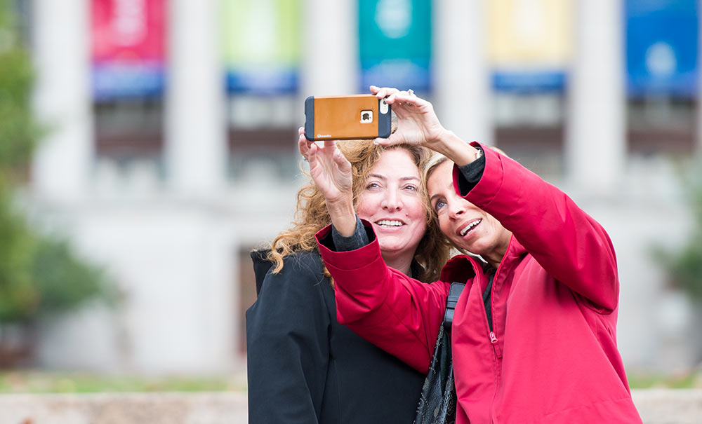 two women taking selfies by library