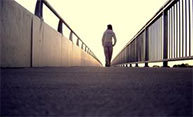 lone woman walking on bridge