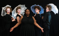 actors in black, some in whiteface with white parasols