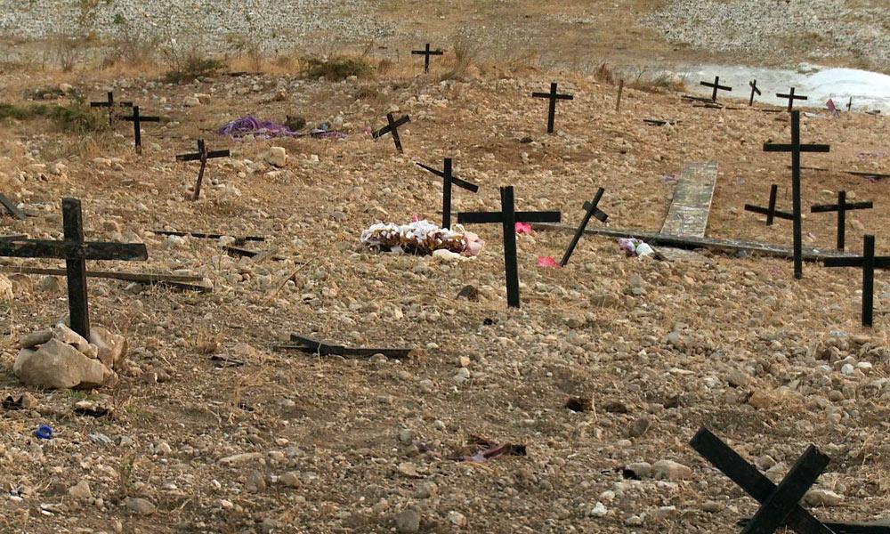 scene of devastation, with crosses marking graves