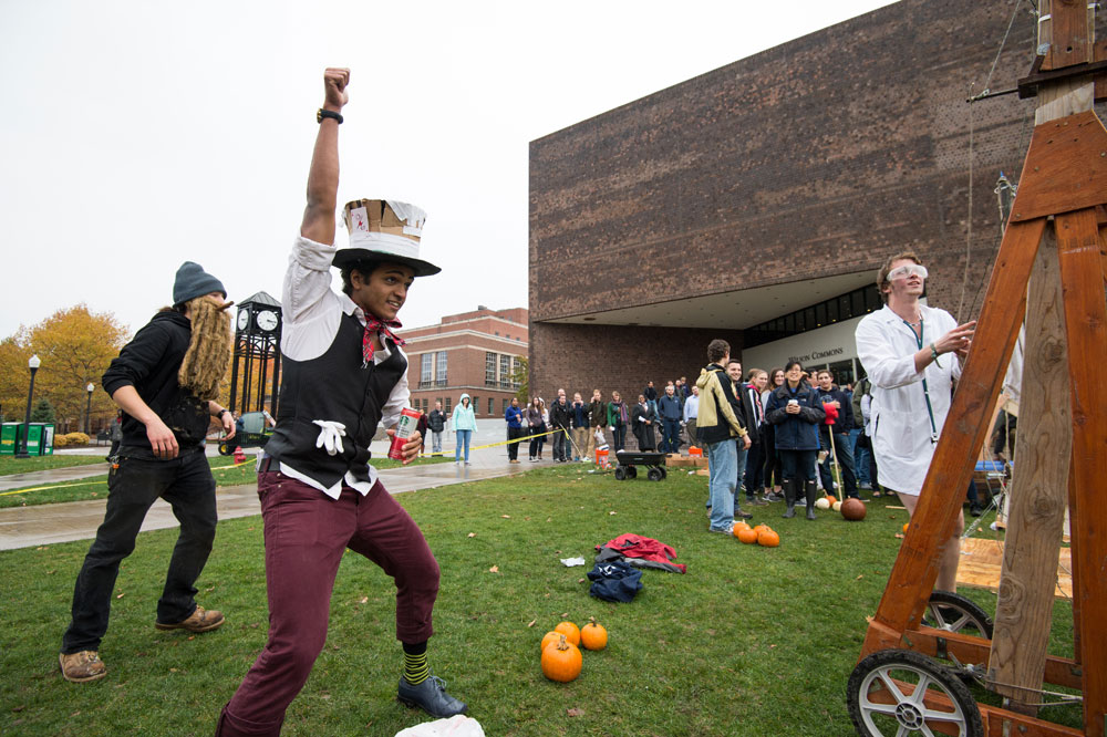 student standing next to a trebuchet and a pile of pumpkins pumps his fist in the air