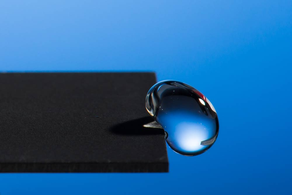photo of a droplet of liquid hanging off the edge of a surface