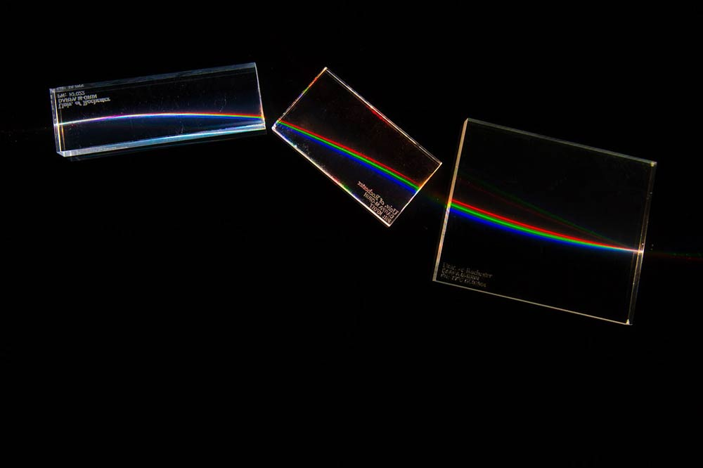 white light passing through three blocks of clear plastic and breaking into red, green, and blue light