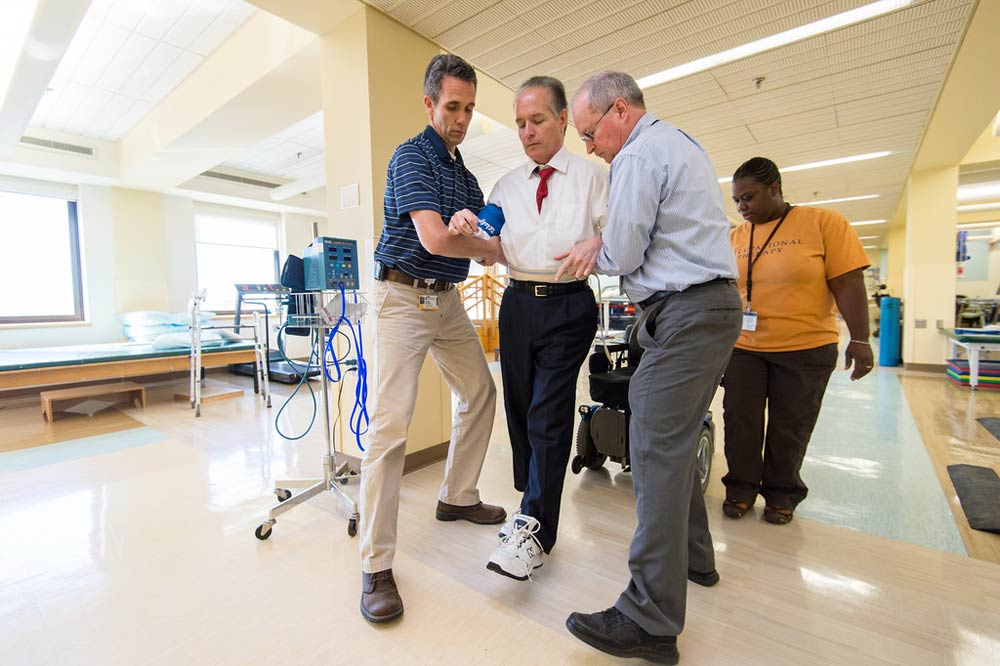 physical therapists assist Bradford Berk as he walks during a therapy session