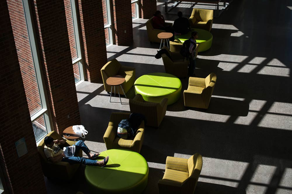 light streaming in through the windows onto the tables and chairs in Rettner Hall