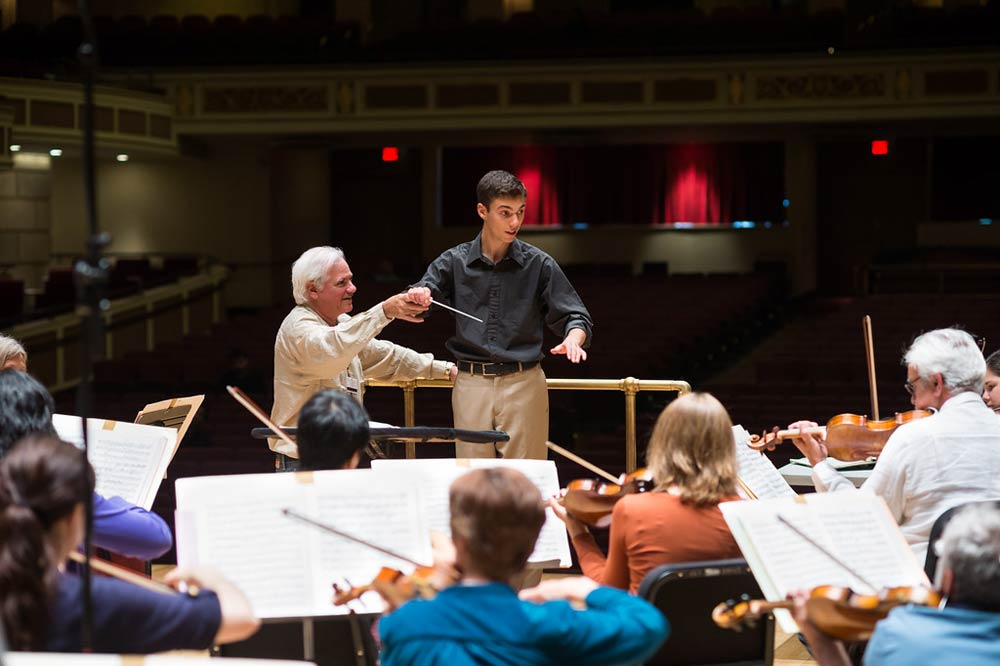 instructor helping a conductor at the front of an orchestra