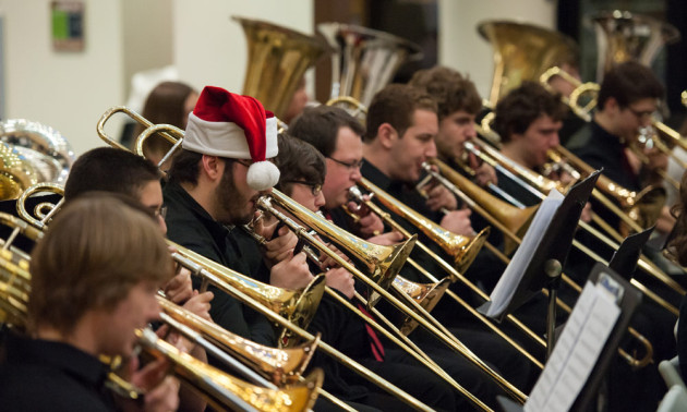 row of musicians playing trombones, one is wearing a Santa hat