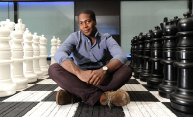 student sitting on a life-sized chess board
