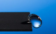 Professor Chunlei Guo has developed a technique that uses lasers to render materials hydrophobic, illustrated in this image of a water droplet bouncing off a treated sample.