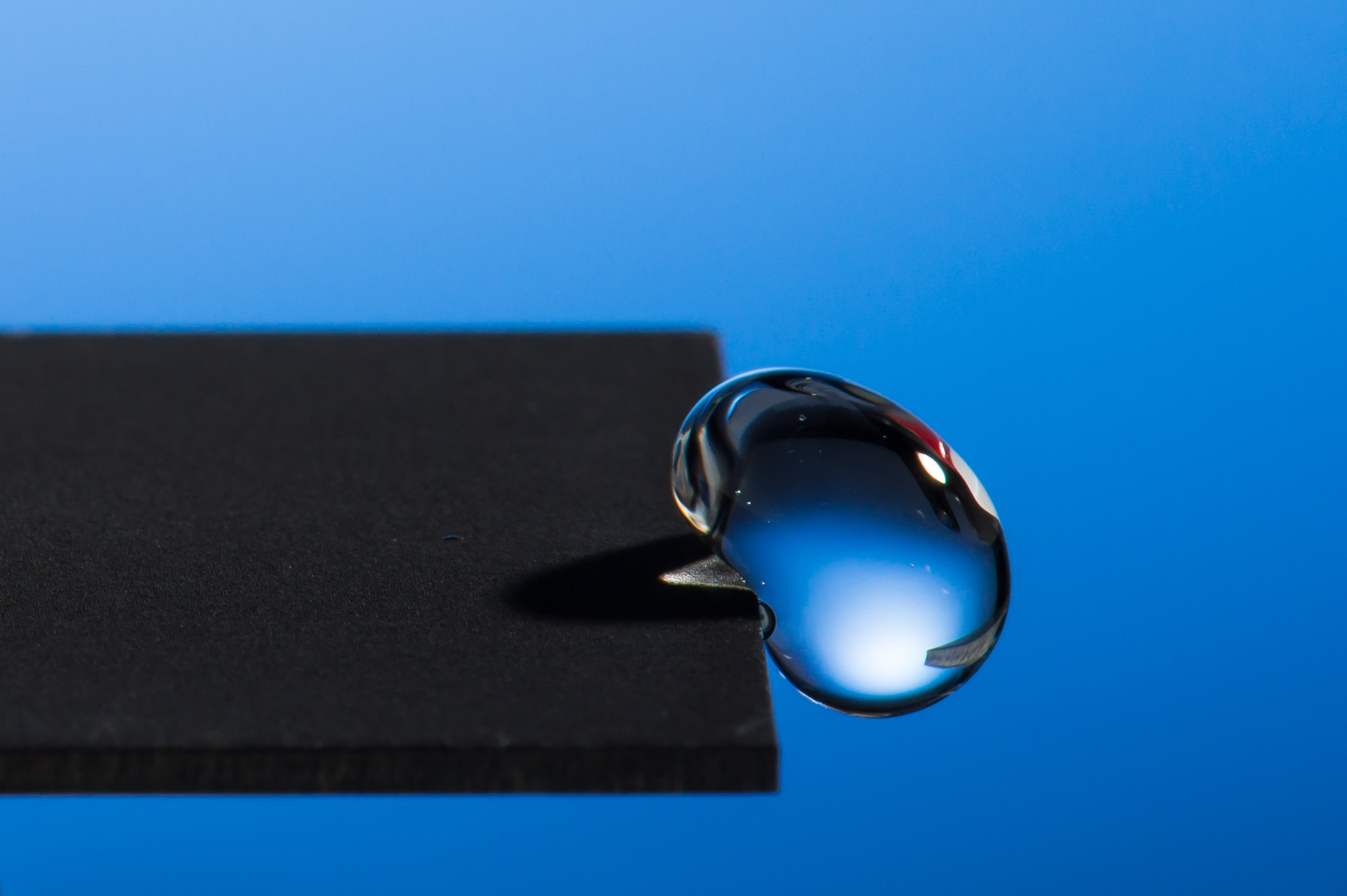 drop of water about to drop off the edge of a metal surface.