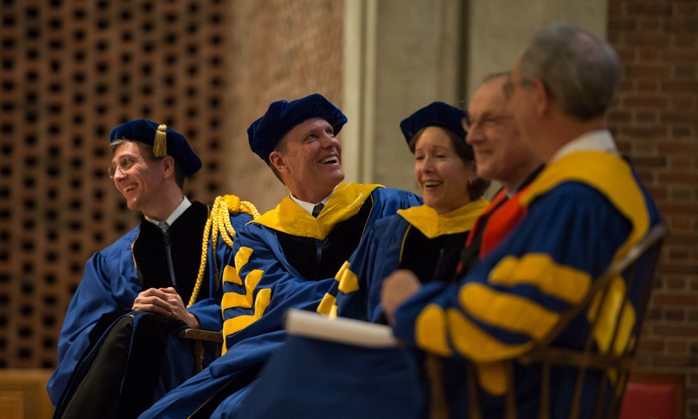 platform party in academic regalia looks over the shoulder at a screen, laughing