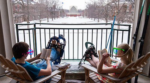 two students wearing snow shows read on the Rush Rhees Library balcony
