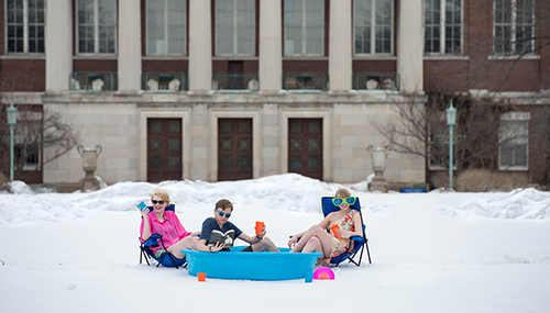 three students sitting in a pool on a snow-covered quad.