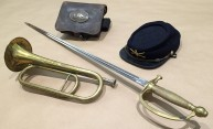 collection of civil war artifacts, including saber, bugle, and cap
