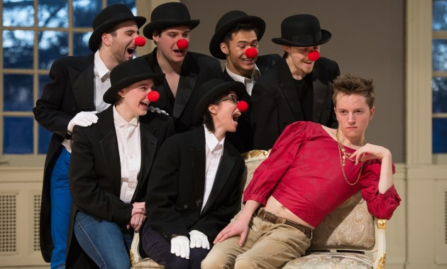 actors sitting on a couch, all but one of them wearing bowler hats and clown noses