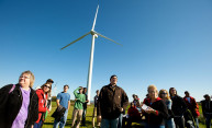 group of people standing in front of a wind turbine