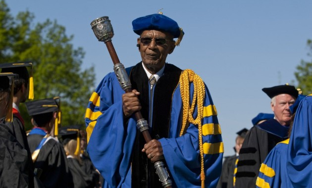 Jesse Moore in academic regalia carries the mace at the head of a commencement procession