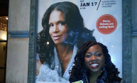 student posing with poster of Audra McDonald outside theater
