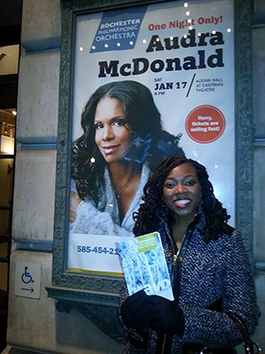 student posing with Audra McDonald poster outside theater