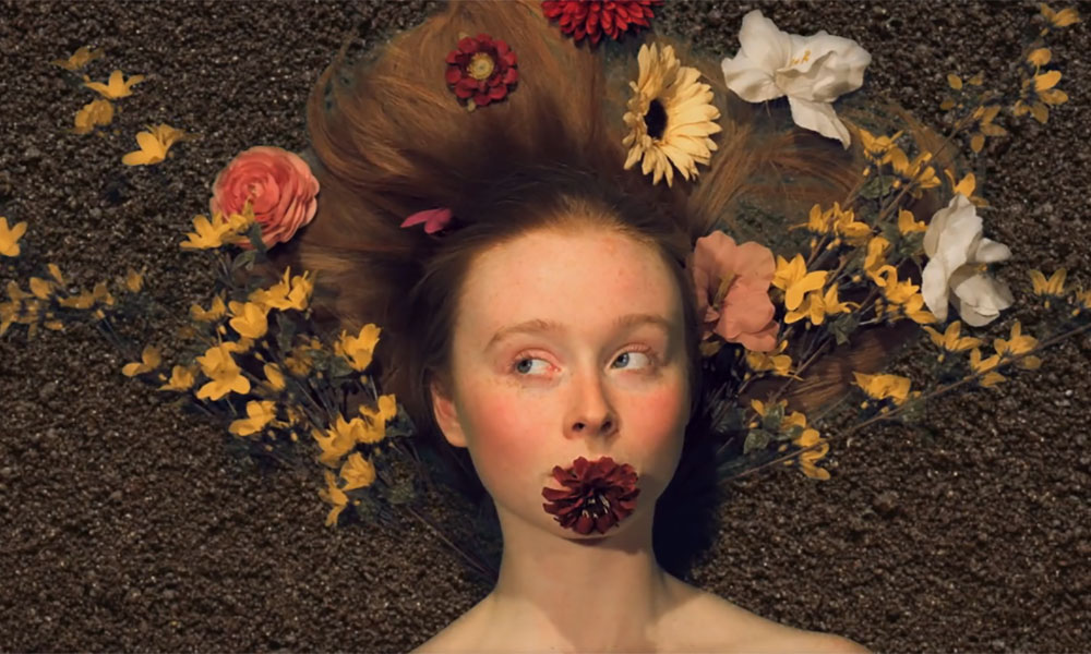 screenshot from film features closeup of woman with flowers in her hair