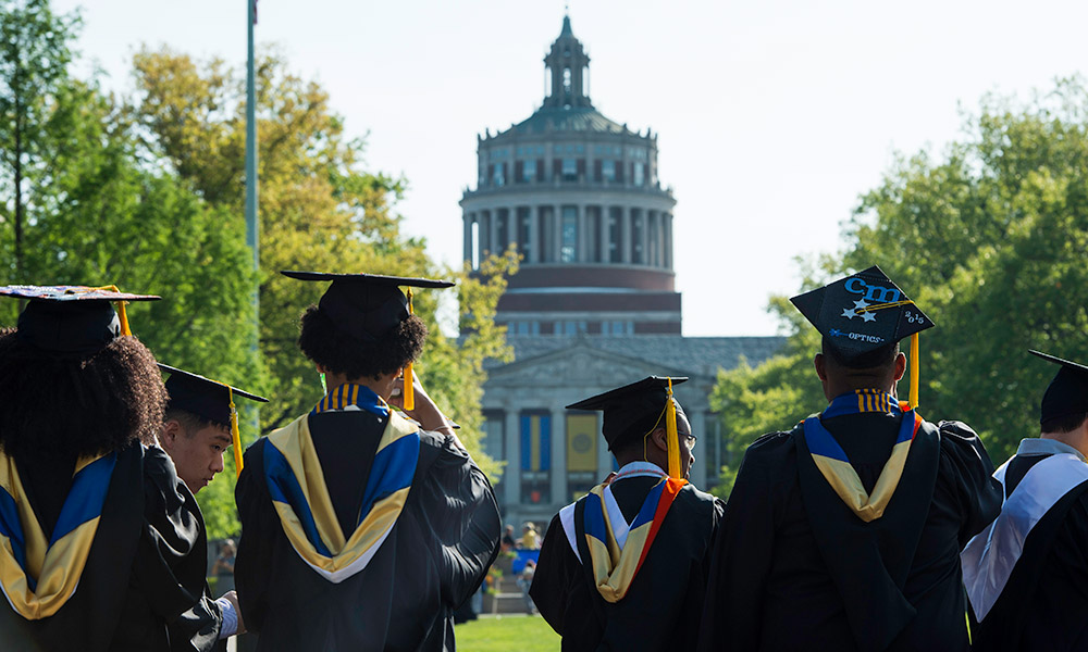 graduates taking photos of Rush Rhees Library
