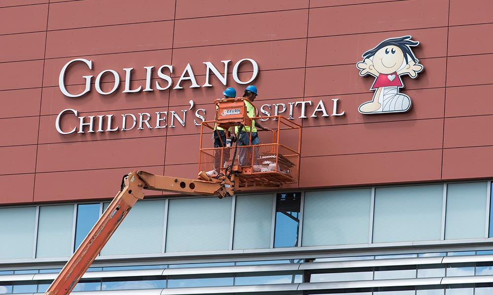 workers in a bucket truck hanging the letters for the Golisano Children's Hospital sign