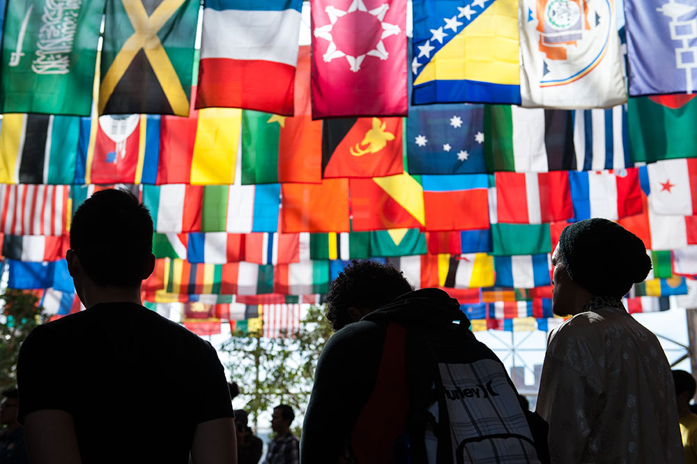 group of students stand solemnly under large grouping of flags