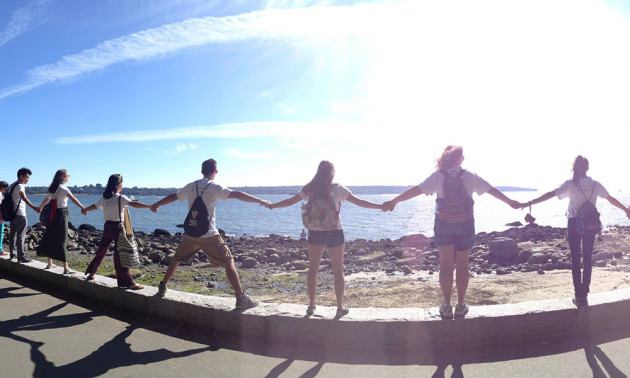 group of students holding hands and looking out over the water