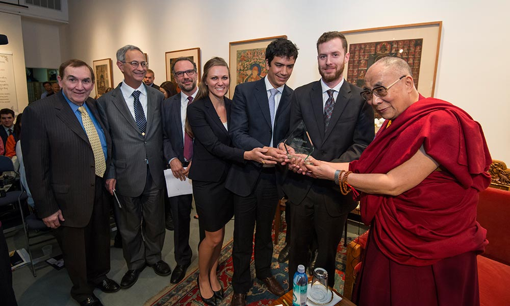 students and administrators pose with Dalia Lama after winning an award