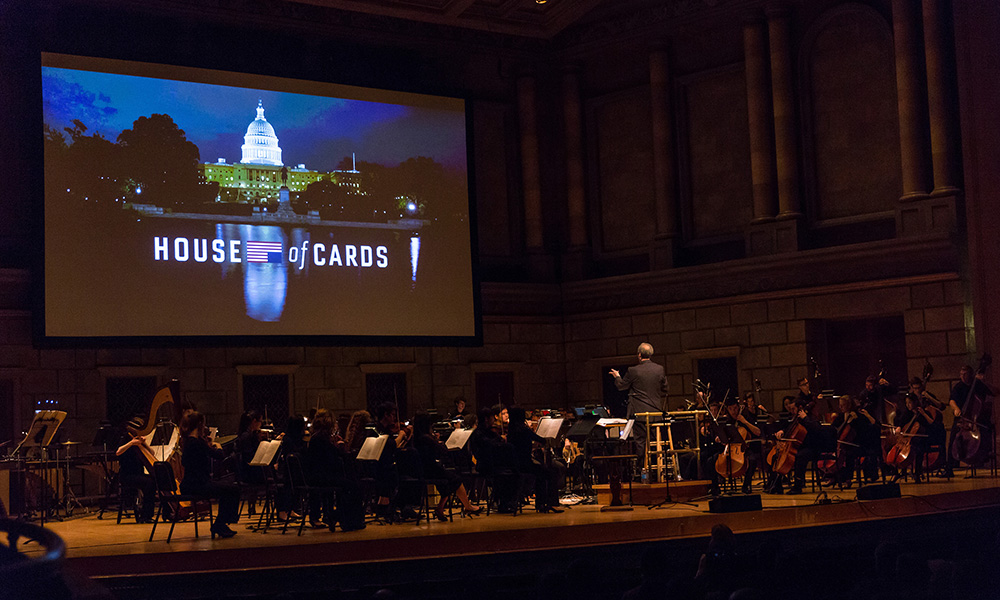 Jeff Beal conducting on stage with large House of Cards title on screen above musicians