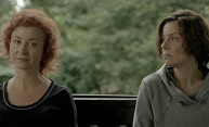 still from film shows two women sitting at a table, with angry expressions on their faces