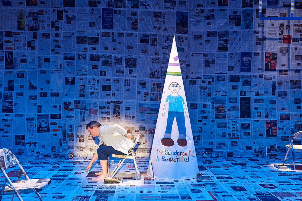 man sits in the spotlight on a stage covered in newspapers