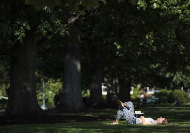 girl reclines on the quad with a book on a sunny day