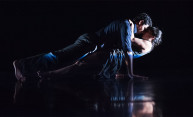 male and female dancer on dark stage